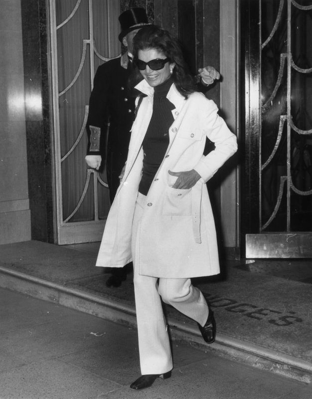 Jackie Onassis (1929 - 1994), widow of American President John F Kennedy and wife of Greek born Argentinian ship owner Aristotle Onassis, leaving Claridges Hotel in London. She is wearing a safari-style jacket over flared hipster trousers and a polo neck jersey. (Photo by Ted West/Getty Images)